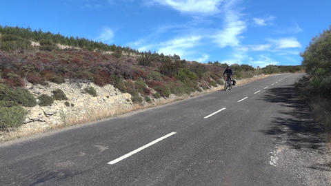 Cyclists coming down the steep slope of a hill covered with dry vegetation 67 Footage