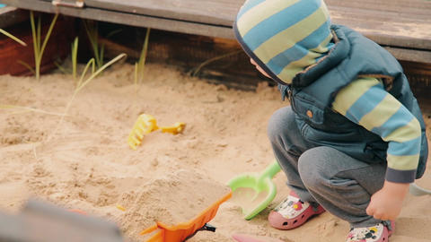 Child in the village playing in a sandbox in cloudy weather Footage