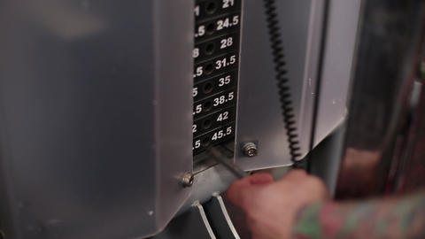 Weighting on the fitness machine in the fitness club Footage