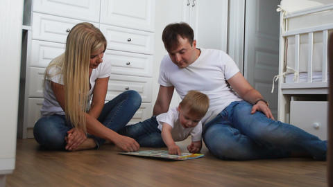 A family of three in white T-shirts and blue jeans sitting on the floor of their Footage