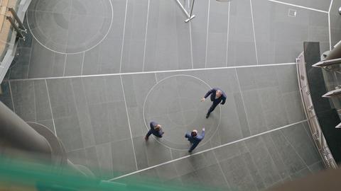 Three Business People Handshaking. Topview GIF