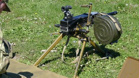 a soldier with a machine gun charges in the summer on the grass Live Action