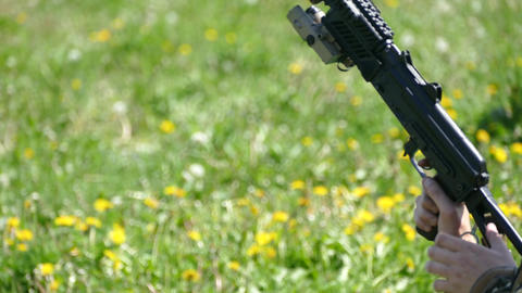 Weapon machine guns and legs of soldiers in summer on the grass Live Action