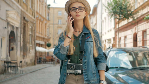 Young cute tourist is talking on the phone outside, wearing hat, glasses Footage