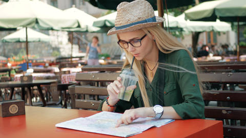 Young tourist woman exploring city map of lviv in cafe and drink while traveling Footage