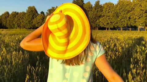 Beauty girl running in a yellow hat on green wheat field over sunset sky ภาพวิดีโอ