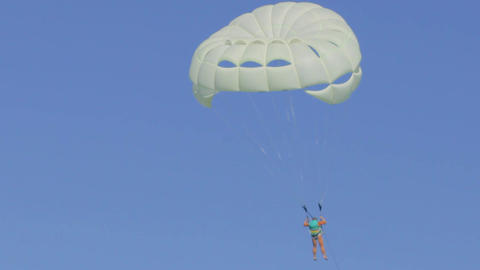 Unrecognizable person flies on white parachute in clear sunny weather ビデオ