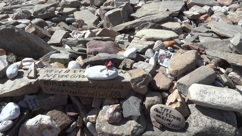 Stones with inscriptions and messages left by pilgrims at the Cruz de Ferro, on  Footage
