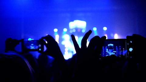 Fans waving their hands and hold the phone with digital displays Footage