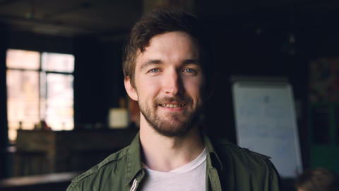 Close-up slow motion portrait of happy bearded guy with dark hair standing in Footage