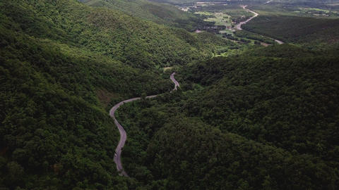 Aerial View of Countryside Road passing through the Mountain Landscape ビデオ