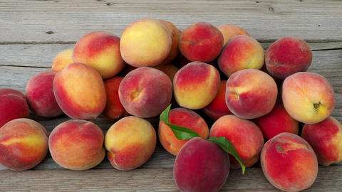Pile of peaches. Ripe peaches fruit on a brown wooden background. 4k resolution Live Action