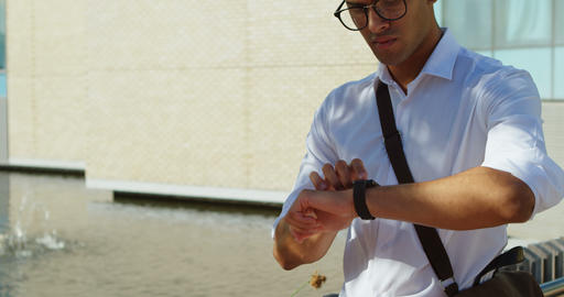 Man in spectacles using smartwatch 4k Live Action
