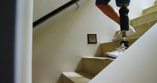 Mature woman with prosthetic leg moving down from stairs 4k Footage
