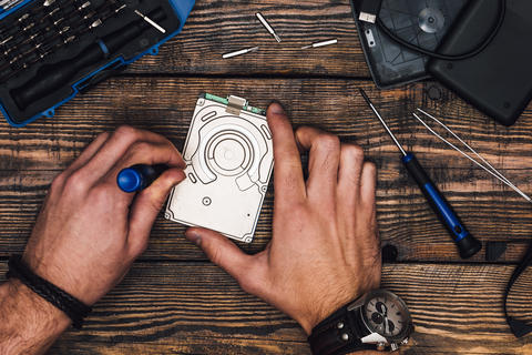 Two Hands with Screwdriver Disassemble HDD Fotografía