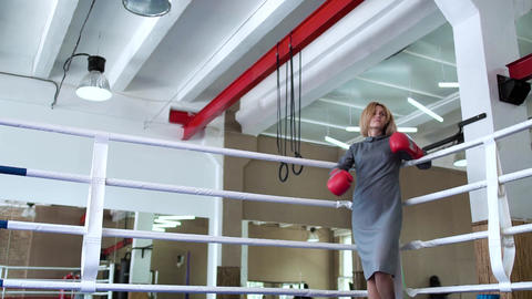 Beautiful businesswoman in elegant dress and boxing gloves at boxing ring Live Action