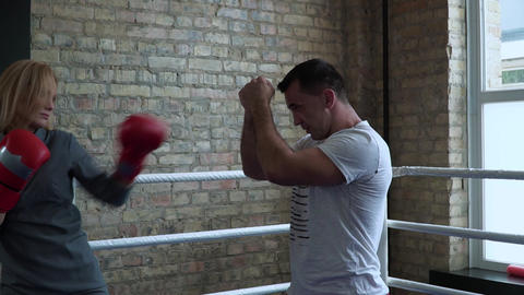 Woman in elegant dress, boxing gloves training with coach at boxing ring Footage