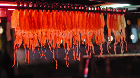 traditional street Asian food, a night food market, squid hanging in a shop Footage