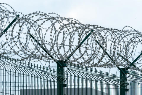 Security fence with a barbed wire. Fence with a barbed wire フォト