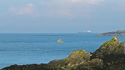 Yellow fishing boat and huge tanker in front of the welsh coast on Anglesey - Footage