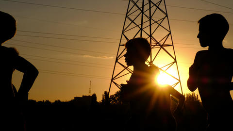 Silhouettes of young boys, jogging on a training against the sunset ビデオ