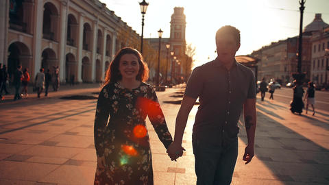 Playful happy young couple is jumping down the street and laughing Footage