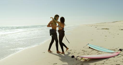 Surfer couple having fun on the beach 4K 4k Live Action