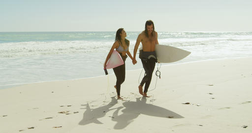 Couple with surfboard walking on the beach 4K 4k Footage