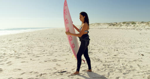 Female surfer putting the surfboard in sand 4K 4k Live Action