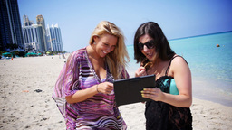 Two Women use an iPad at the Beach, Outdoors Footage