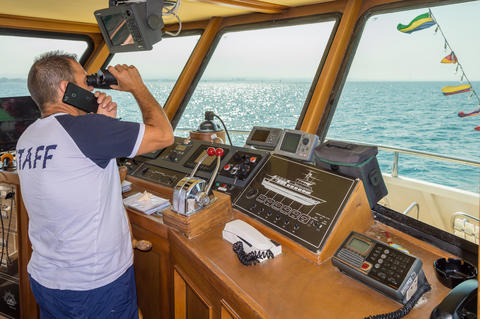 Captain in the post of a ship watching with binoculars on the Ad Photo