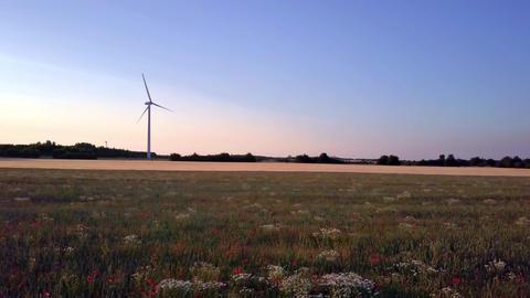 Aerial footage of a wind turbine in the background - drone flying sideways ビデオ