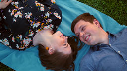 Happy young adult couple lying on the grass over sunset. Attractive Girl near Footage