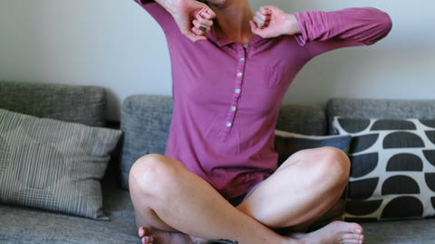 Woman stretching and yawning while waking up in living room 4k Live Action