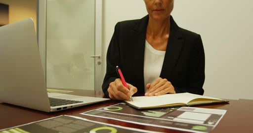 Businesswoman writing on a diary at desk 4k Footage