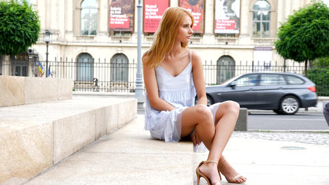 Gorgeous beautiful young woman model sitting on the stairs Live Action