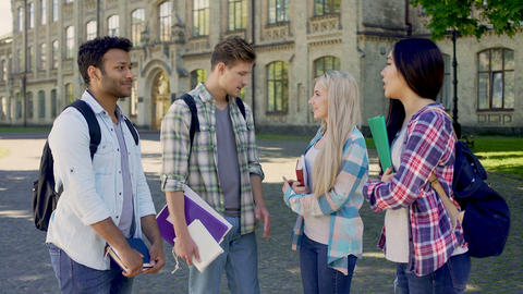 Two senior students inviting cheerful multiethnic fellowmates to college party Footage