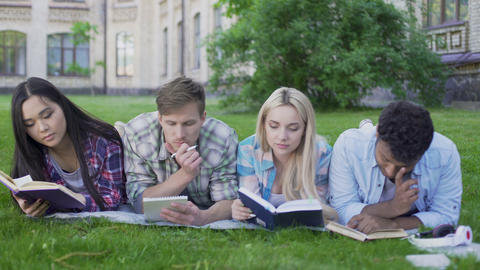 Friends preparing for exams, reading materials in university garden, education Live Action