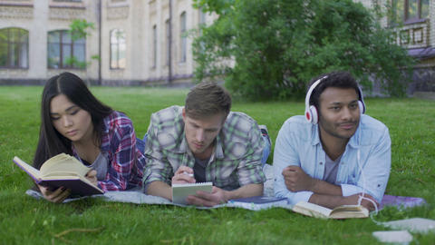 Multi-ethnic team relaxing, enjoying wonderful pastime on campus, togetherness Footage
