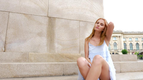 Sexy amazing model posing at the camera sitting on the stairs outdoor Footage