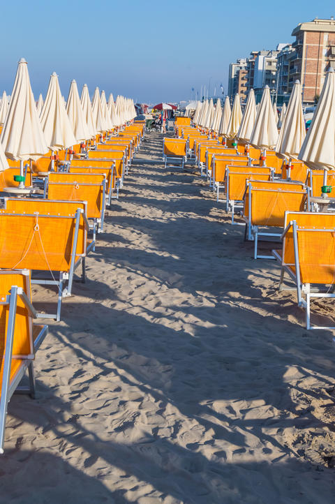 Rows of orange umbrellas and deckchairs on the beach Photo