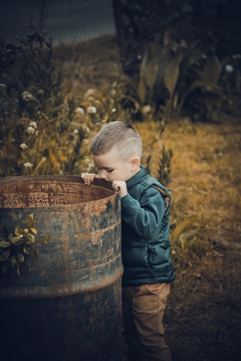 The boy stands near a rusty metal empty barrel Photo