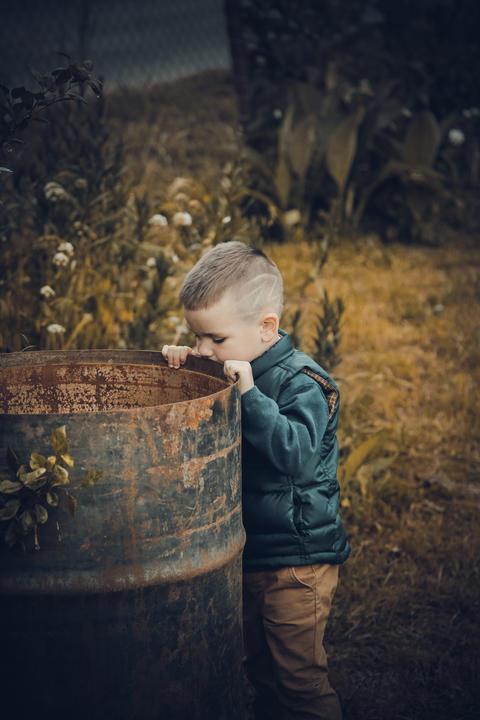 The boy stands near a rusty metal empty barrel フォト