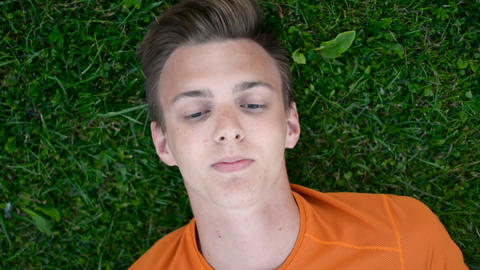 Close up portrait of young boy teenager resting on the grass dreaming, thinking Footage