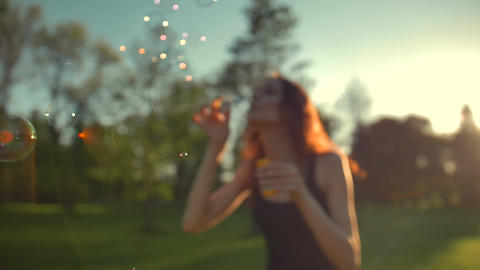 Portrait of beautiful ginger young woman. Blowing bubble in the park Footage