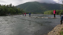 Travelers and tourists cross mountain river on suspension bridge. Time lapse Footage