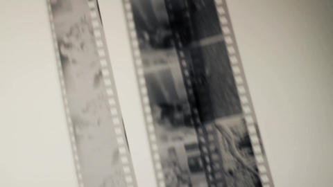 Viewing photos on the film on a light grey background Live Action