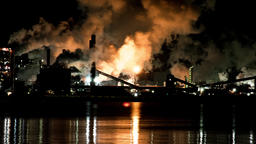 Time lapse of Industrial steel mill at night in the city over looking water ビデオ