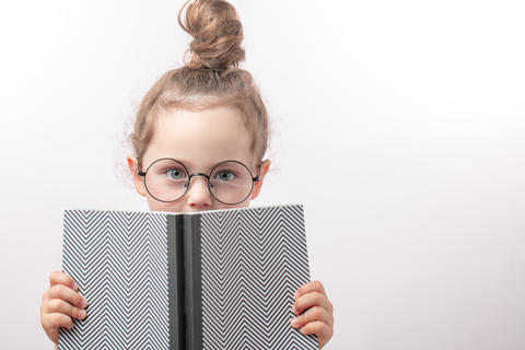 clever beautiful girl with green eyes in round glasses holding a book Fotografía