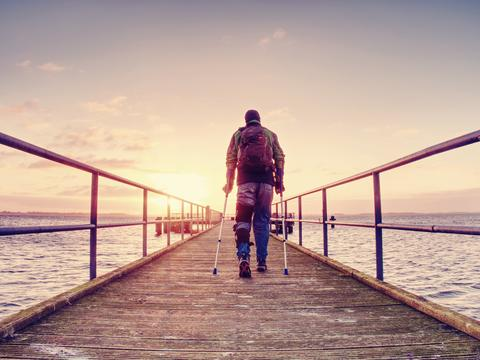 Hurt man with hooded jacket and forearm crutches standing on sea bridge Fotografía